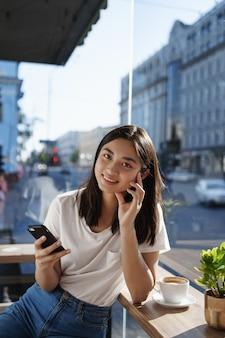Mulher jovem tomando café em um restaurante num dia de verão, conversando no smartphone