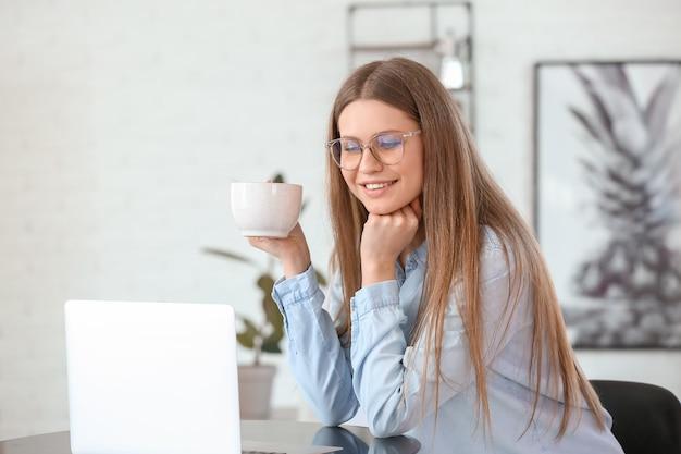 Mulher jovem tomando café enquanto trabalha em um laptop no café