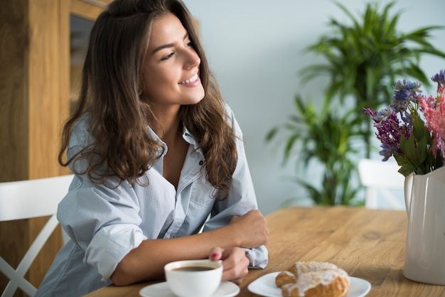 Mulher jovem tomando café na sala de jantar