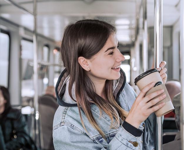 Mulher jovem tomando café no transporte público