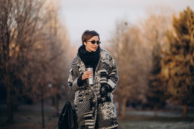 Mulher jovem tomando café pela manhã e caminhando no parque