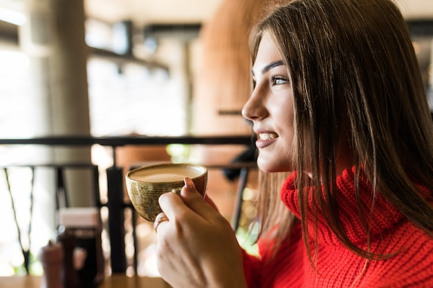 Mulher jovem tomando café pela manhã no restaurante