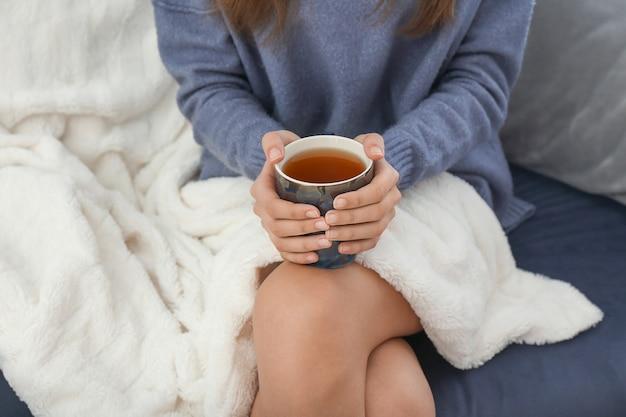 Mulher jovem tomando chá quente em casa