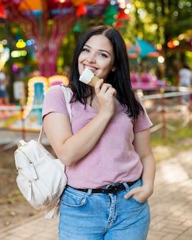 Mulher jovem tomando sorvete lá fora