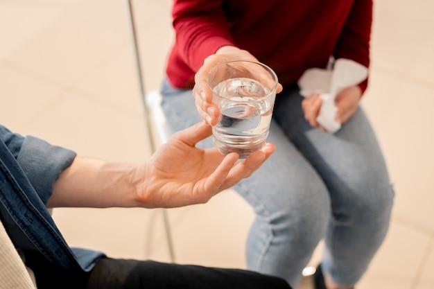 Mulher jovem tomando um copo d'água da mão de um colega de grupo durante uma sessão de terapia psicológica