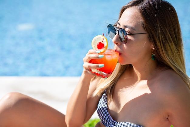 Mulher jovem tomando uma bebida refrescante à beira da piscina usando óculos escuros no verão