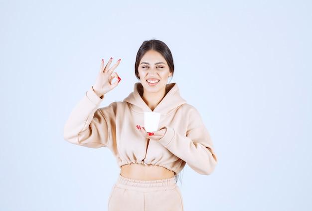 Mulher jovem tomando uma xícara de café e mostrando sinal de prazer