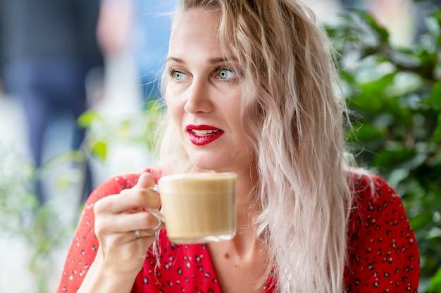 Mulher jovem tomando uma xícara de café em um café