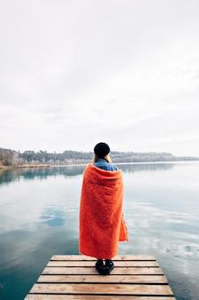 Mulher jovem tomando uma xícara de café na margem do lago