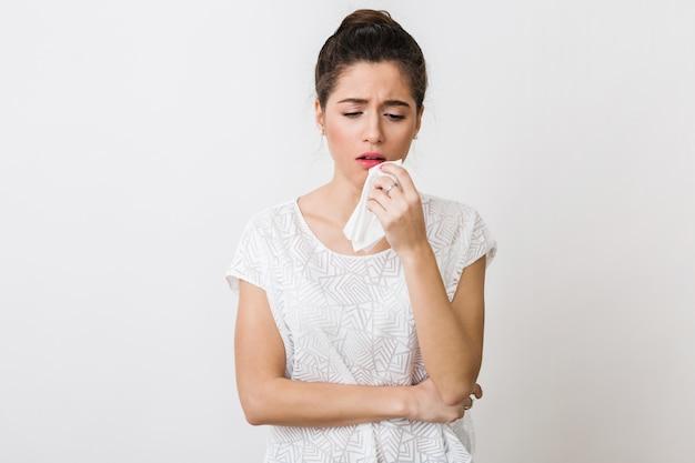 Mulher jovem tossindo com um guardanapo, resfriada, sentindo-se doente,, isolada