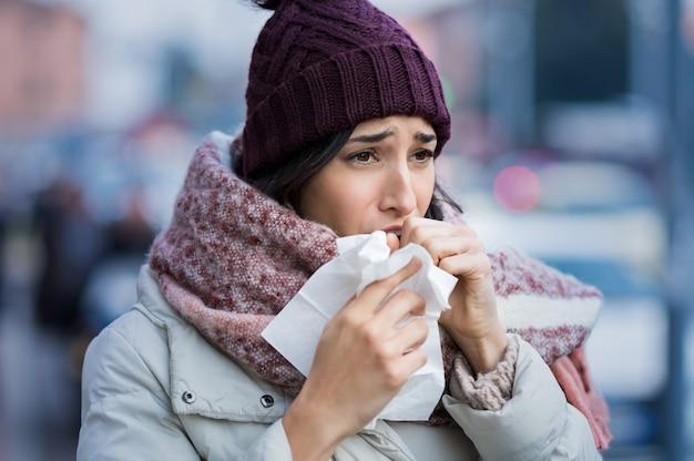 Mulher jovem tossindo durante o inverno na rua