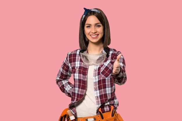 Mulher jovem trabalhador apertando as mãos para fechar um bom negócio na parede rosa isolada