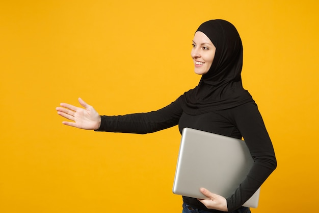 Mulher jovem trabalhador árabe muçulmano em roupas pretas de hijab segurar nas axilas laptop pc isolado no retrato de parede amarela. conceito de estilo de vida religioso de pessoas.