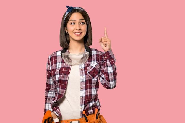 Mulher jovem trabalhador que pretende realizar a solução enquanto levanta um dedo na parede rosa isolada