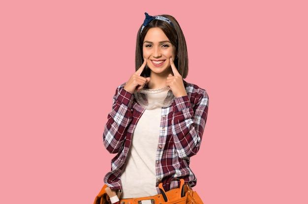 Mulher jovem trabalhador sorrindo com uma expressão feliz e agradável na parede rosa isolada