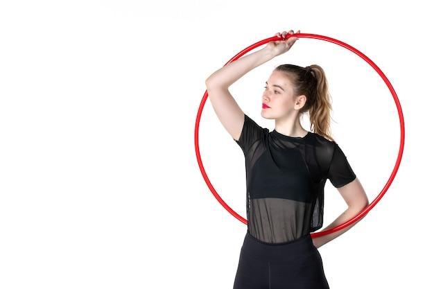 Mulher jovem trabalhando com bambolê vermelho na parede branca cor de estilo de vida saúde corpo ioga esporte atleta mulher de frente