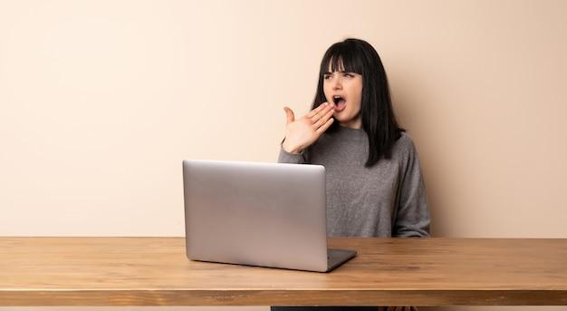 Mulher jovem, trabalhando, com, dela, laptop, bocejar, e, cobertura, boca aberta, com, mão