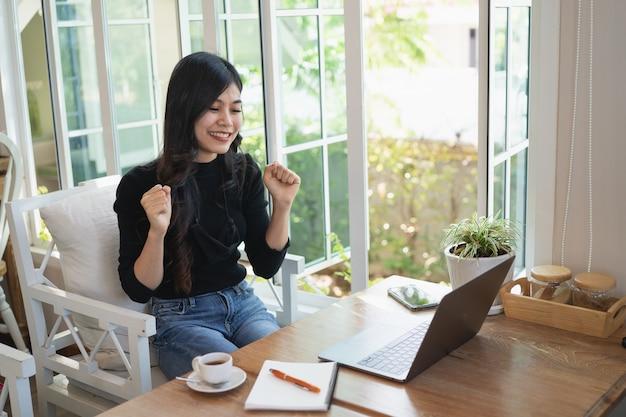 Mulher jovem trabalhando com o laptop na mesa de madeira em casa