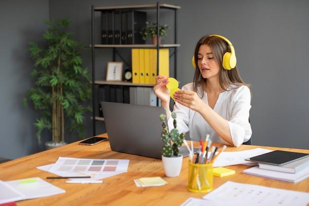 Mulher jovem trabalhando com seus fones de ouvido