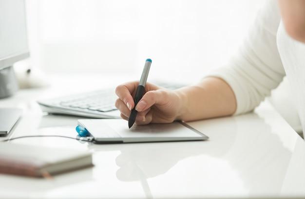 Mulher jovem trabalhando com tablet gráfico digital