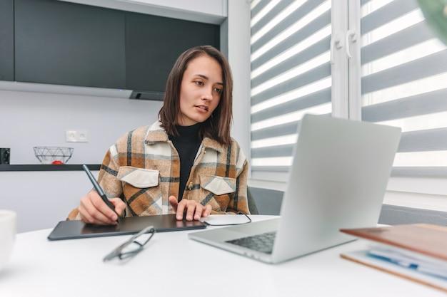 Mulher jovem trabalhando com tablet gráfico em casa olhando para um laptop