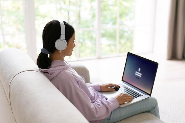 Mulher jovem trabalhando em seu laptop em casa