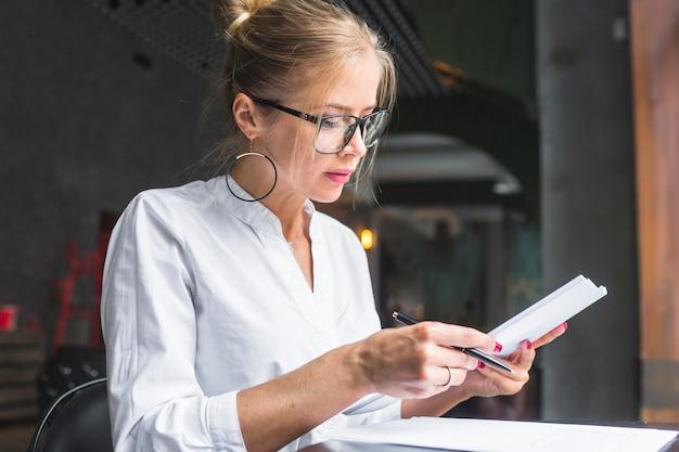 Mulher jovem, trabalhando, ligado, documento, em, restaurante