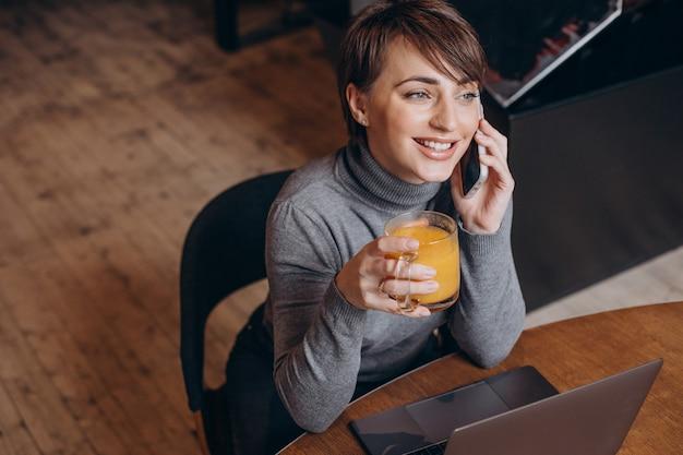Mulher jovem trabalhando no computador e bebendo chá quente