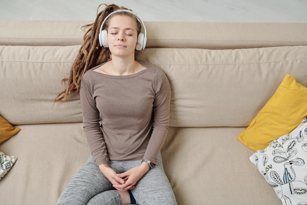 Mulher jovem tranquila com fones de ouvido ouvindo música para meditação no sofá, se divertindo