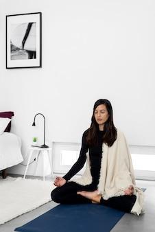 Mulher jovem tranquila em roupas esportivas e xale praticando meditação na pose de lótus em um quarto de estilo minimalista em casa