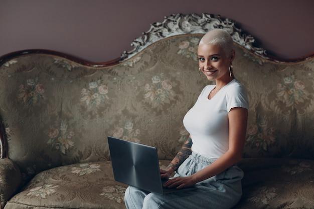 Mulher jovem treinando com cabelo curto loiro sentado e sorrindo com o laptop no sofá vintage