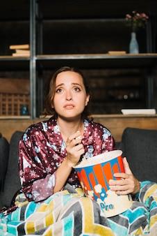 Mulher jovem triste assistindo televisão