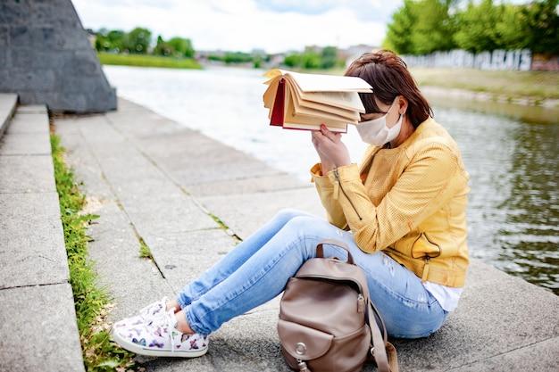 Mulher jovem triste com roupas casuais e máscara protetora, cansada, segura o livro na cabeça enquanto está sentada perto de um rio na margem de uma cidade deserta