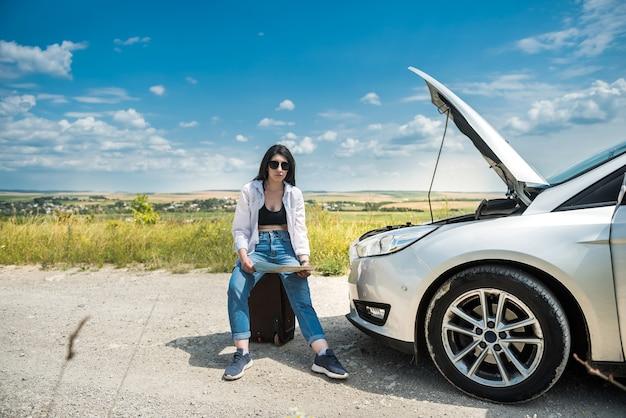 Mulher jovem triste e à espera de ajuda perto de um carro danificado