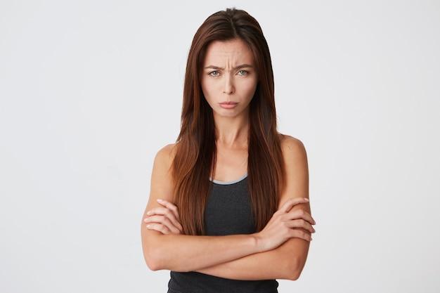 Mulher jovem triste e chateada com cabelo comprido e os braços cruzados e parecendo ofendida