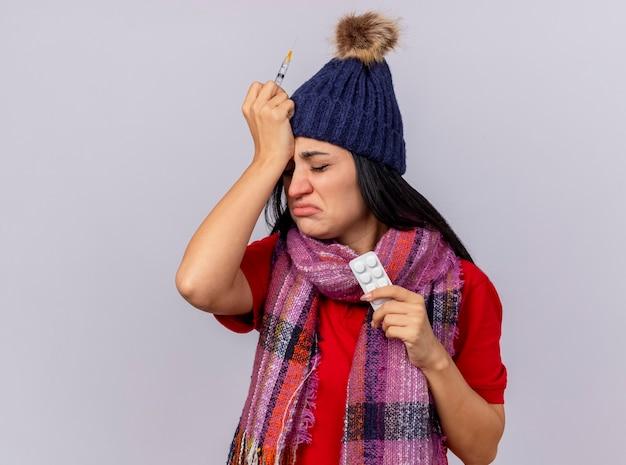 Mulher jovem triste e dolorida com chapéu e lenço de inverno, segurando uma seringa e um pacote de comprimidos, mantendo a mão na cabeça isolada na parede branca