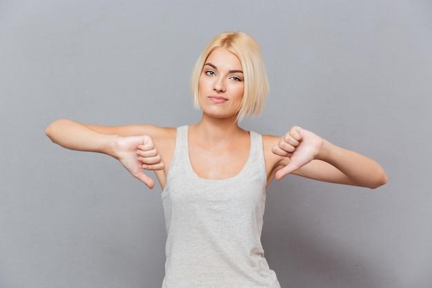 Mulher jovem triste e infeliz mostrando os polegares para baixo com as duas mãos sobre a parede cinza