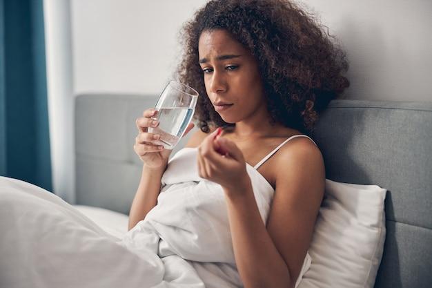 Mulher jovem triste segurando um comprimido e um copo d'água