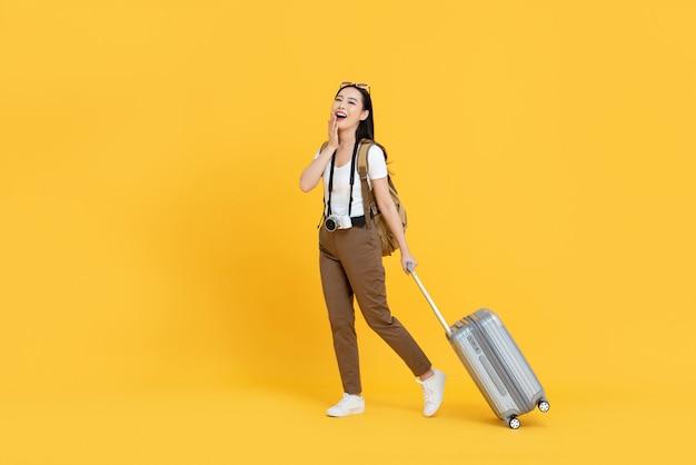 Mulher jovem turista asiática com bagagem vai viajar de férias