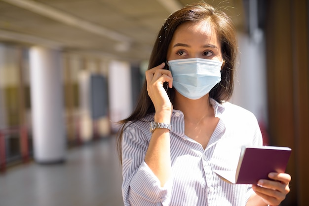 Mulher jovem turista asiática com máscara falando ao telefone enquanto segura o passaporte no aeroporto