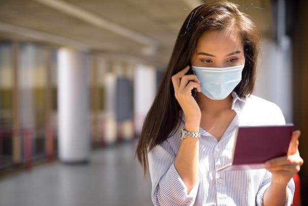 Mulher jovem turista asiática com máscara falando ao telefone enquanto verifica o passaporte no aeroporto