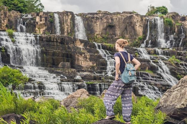 Mulher jovem, turista, caminhante no fundo da incrível cachoeira de pongour