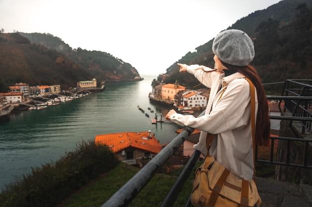 Mulher jovem turista caucasiana, olhando para a baía de um ponto de vista elevado em pasaia, país basco.