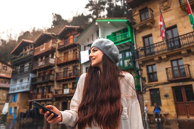 Mulher jovem turista caucasiana usando o smartphone em uma cidade velha.
