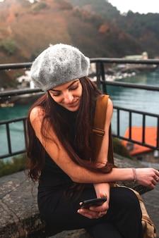 Mulher jovem turista caucasiana usando o smartphone sentou-se em um banco junto ao mar.