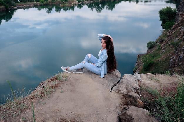 Mulher jovem turista está sentada no topo do monte e olhando para uma bela paisagem. caminhada mulher relaxando no topo do penhasco desfrutando. garota atraente em roupas jeans