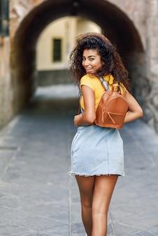 Mulher jovem turista negro com penteado encaracolado ao ar livre