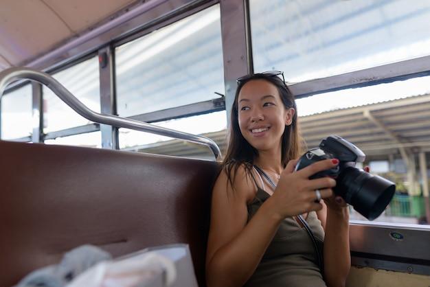 Mulher jovem turista sentada no ônibus enquanto usa uma câmera dslr
