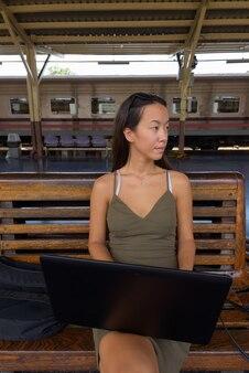 Mulher jovem turista sentada usando um laptop