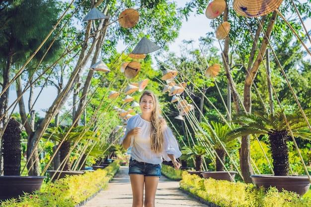 Mulher jovem turística e chapéus vietnamitas viajam pelo conceito do vietnã